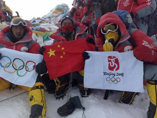 Chinese climbers display flags at the top of the 8844.43-meter summit of Mt. Qomolangma in southwest China's Tibet Autonomous Region on May 8, 2008.(Xinhua Photo)