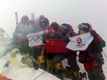 Chinese climbers display an Olympic torch, an Olympic flame lantern, a flag of International Olympic Committee, a Chinese National flag and a flag of the 29th Olympic Games at the top of the 8844.43-meter summit of Mt. Qomolangma in southwest China's Tibet Autonomous Region on May 8, 2008. (Photo credit: Ngawang Chagxi/Xinhua)