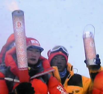 "TV grab from May 8, 2008 shows Female climber Cirenwangmu displays the Beijing Olympic torch ""Xiangyun"" at the top of the 8844.43-meter summit of Mt. Qomolangma in southwest China's Tibet Autonomous Region on May 8, 2008. (Photo credit: Xinhua)"